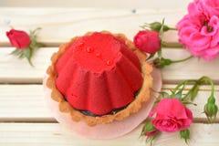 充分甜点和红色蛋糕在桃红色玫瑰背景的巧克力 近小蛋糕在木纹理上升了 免版税库存图片