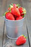 充分用桶提在木背景的草莓 免版税库存图片