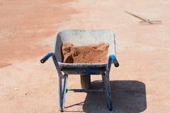 充分电烙推车在建造场所的沙子 库存图片