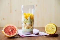 充分白色搅拌器新鲜水果和切的葡萄柚在厨房工作台面 库存图片