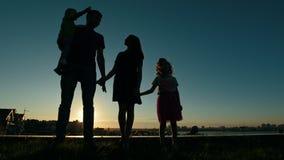 充分的家庭-父亲、母亲、女儿和小儿子画象-在日落的剪影,在地平线前面 股票视频