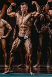 充分的成长的人爱好健美者展示二头肌和腹肌 库存照片