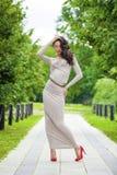 充分的成长,性感的长的灰色礼服的美丽的少妇 免版税库存图片