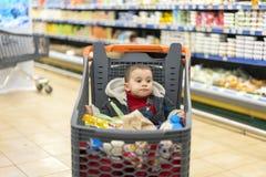充分的推车用食物在超级市场 在推车坐婴孩 免版税库存图片