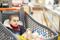 充分的推车用食物在超级市场 在推车坐婴孩 库存照片