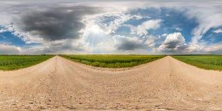 充分的无缝的球状hdri全景360度在柏油路的角度图在领域中在与令人敬畏的云彩的夏日 库存照片