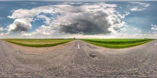 充分的无缝的球状hdri全景360度在柏油路的角度图在领域中在与令人敬畏的云彩的夏日 图库摄影