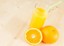 充分的杯与秸杆的橙汁在与空间的果子桔子附近文本的 免版税库存图片