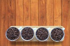充分的杯子堆在木桌上的咖啡豆与从顶视图的拷贝空间 库存照片
