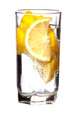 充分的杯水用在白色查出的柠檬 免版税库存照片