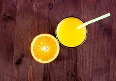 充分的杯看法上面与秸杆的橙汁和半橙色与文本的空间 免版税库存图片