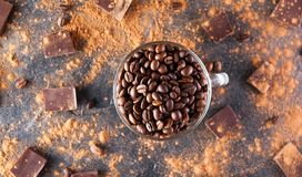 充分的玻璃杯子Roasted在黑暗的石背景的咖啡豆与消散巧克力可可粉、片断和豆 有选择性 库存照片