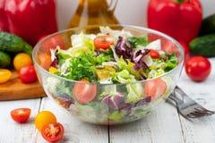 充分的碗新蔬菜沙拉关闭在反对白色背景的一张轻的桌上在一个土气厨房 有用的概念和simpl 免版税库存图片