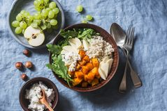 充分的碗用被烘烤的白薯、大麦、芝麻菜和苹果 素食主义者有秋天菜和五谷的菩萨碗,在bl 免版税图库摄影