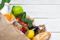 充分的纸袋在白色木背景的另外健康素食食物 水果、蔬菜、坚果、面包和牛奶 免版税库存图片