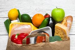 充分的纸袋在白色木背景的另外健康食物 水果、蔬菜、鱼和鸡肉 免版税库存照片