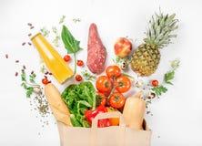 充分的纸袋在白色背景的健康食物 免版税库存照片