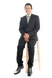 充分的身体亚洲商人坐椅子 免版税图库摄影