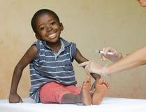 充分的身体得到针射入的射击了一个愉快的非洲黑人孩子作为医疗接种 免版税图库摄影