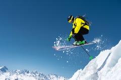 充分的运动器材的一个滑雪者跳进悬崖从冰川的顶端以蓝色为背景 免版税库存照片