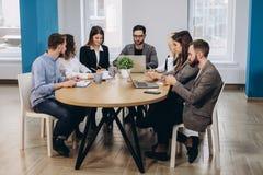 充分的集中在工作 公司工作在现代办公室的队工作的同事 免版税库存照片