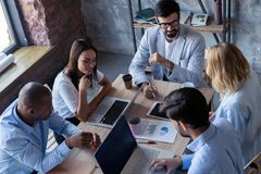 充分的集中在工作 沟通小组年轻的商人工作和,当坐在办公桌时 库存图片