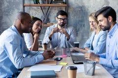 充分的集中在工作 沟通小组年轻的商人工作和,当坐在办公桌时 免版税库存图片