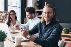 充分的集中在工作 聪明的cas的年轻现代同事 免版税库存照片