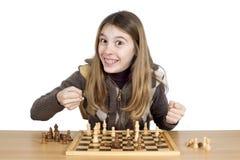 充分看与大微笑的照相机和眼睛与两个握紧拳头的喜悦的年轻激动的女孩在棋比赛期间 免版税图库摄影