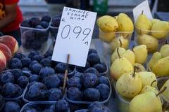 充分箱子与卖在梨和桃子旁边的多灰尘的白色蜡状的涂层的新鲜的黑琥珀色的李子在地方城市水果市场上 免版税库存照片