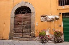 充分红色自行车站立在一个老木门前面的花 免版税库存图片