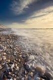 充分美好的海滩场面在海岸线的小卵石 图库摄影