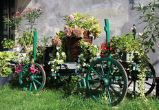 有五颜六色的花的老木推车 免版税库存图片