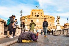 充分要求叫化子的妇女在她的膝盖的施舍在蓬特桑特'安吉洛,哈德良桥梁有圣天使城堡的走的人, 免版税图库摄影