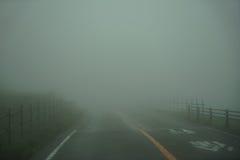 充分车行道和篱芭看法白色雾,当驾驶通过地方路在阿苏山地区时的多雨和恶劣天气天 免版税库存照片