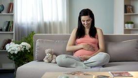 充分轻轻地接触她心爱的怀孕的肚子的母性本能妇女 库存图片
