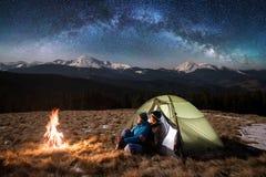 充分野营的游人在晚上,有休息在营火和帐篷附近在夜空下星和银河 图库摄影