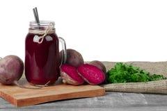 充分金属螺盖玻璃瓶甜菜根圆滑的人,明亮的紫色甜菜,在白色背景隔绝的绿色芬芳荷兰芹 库存图片