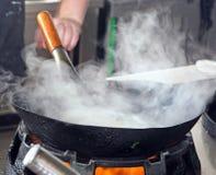 充分铁锅在烹调期间的蒸汽 免版税库存照片