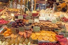充分食品店陈列室干果子、五颜六色的甜点和酒精与价格 免版税图库摄影