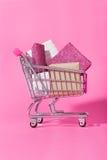 充分购物台车在桃红色背景的被包裹的礼物 图库摄影