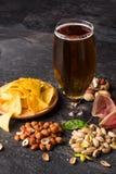 充分贮藏啤酒黑啤酒 芯片、咸坚果和肉用冷的酒精啤酒在黑桌背景 复制空间 免版税库存照片