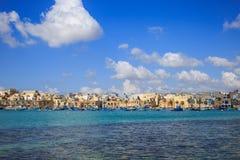 充分Marsaxlokk历史的口岸小船在马耳他 与少量白色云彩和村庄背景的蓝天 地区莫斯科一幅全景 免版税库存照片