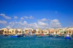 充分Marsaxlokk历史的口岸小船在马耳他 与少量白色云彩和村庄背景的蓝天 地区莫斯科一幅全景 库存照片