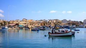 充分Marsaxlokk历史的口岸小船在马耳他 蓝天和村庄背景 免版税库存图片
