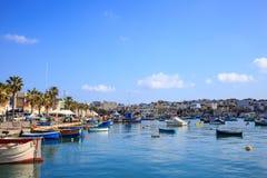 充分Marsaxlokk历史的口岸木小船在马耳他 蓝天和村庄背景 库存照片