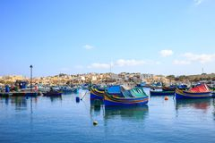 充分Marsaxlokk历史的港口木小船在马耳他 蓝天和村庄背景 库存照片