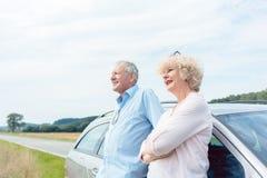 充满信心地微笑两资深的人,当倾斜在他们的汽车时 库存图片