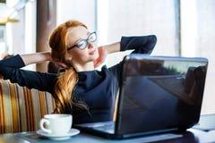 充满好心情的华美的快乐的妇女自由职业者使用距离工作的便携式计算机在咖啡馆酒吧的午餐期间 图库摄影