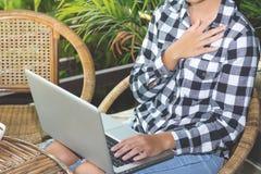 充满强的胸口痛的女实业家,当坐在您的书桌时 免版税库存图片